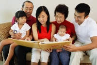 Three generation family, looking at photo album - Jade Lee