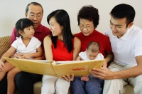 Three generation family, sitting side by side and looking at photo album - Jade Lee