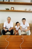 Young girl sitting between father and grandfather while they play video games - Jade Lee