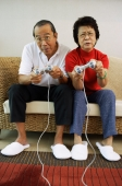 Mature couple sitting on sofa playing video games, frowning - Jade Lee