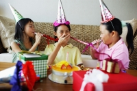 Three girls with noisemakers and party hats - Jade Lee