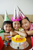 Three girls with party hats in front of birthday cake - Jade Lee