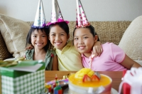 Three girls with party hats sitting side by side - Jade Lee