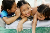 Three girls at edge of pool, one whispering to the girl next to her - Jade Lee