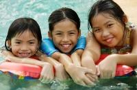 Three girls in swimming pool, looking at camera - Jade Lee