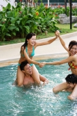 Couples playing in swimming pool, women sitting on men's shoulders - Jade Lee