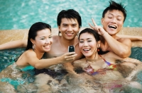 Couples in swimming pool, looking at mobile phone - Jade Lee
