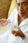 Mature man holding glass of water and pills - Jade Lee