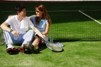 Couple sitting down on tennis court, looking at each other - Alex Microstock02