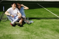 Couple sitting down on tennis court, side by side - Alex Microstock02
