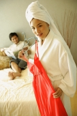 Man lying on bed, woman in robe holding red dress in front of her - Alex Microstock02