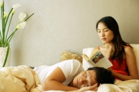 Woman on bed, reading a book, man lying on her lap - Alex Microstock02