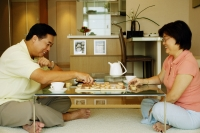Couple sitting on floor, playing Chinese chess at home - Alex Microstock02