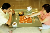 Couple sitting on floor, playing Chinese chess at home, high angle view - Alex Microstock02