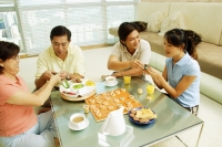 Family sitting in living room with food and board game on table in front of them. - Alex Microstock02