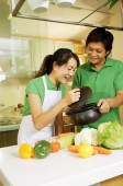 Couple in kitchen, woman lifting lid of pot and looking in - Alex Microstock02