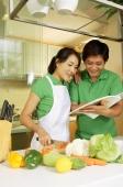 Couple in kitchen, looking through cookbook - Alex Microstock02