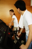 Couple in gym using treadmill, looking at each other - Alex Microstock02