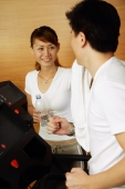 Couple in gym, man on treadmill, woman holding bottle of water looking at him - Alex Microstock02