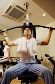 Man using exercise machine, low angle view - Alex Microstock02