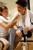 Couple in gym, resting, woman wiping man's face with towel - Alex Microstock02