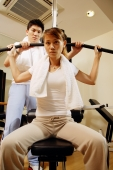 Couple in gym, man helping woman with exercise machine - Alex Microstock02