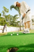 Senior man playing golf on putting green - Alex Microstock02