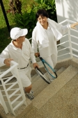 Senior couple walking up stairs, holding tennis rackets - Alex Microstock02