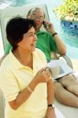 Woman holding coffee mug, man on lounge chair, using mobile phone - Alex Microstock02