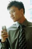 Businessman holding mobile phone, looking away - Alex Microstock02