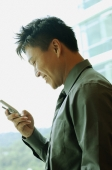 Businessman holding mobile phone, text messaging - Alex Microstock02