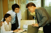 Businessman showing laptop to couple in front of him - Alex Microstock02