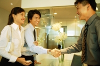 Two businessmen shaking hands, woman holding the arm of one of them - Alex Microstock02