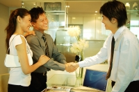 Two men shaking hands, woman holding arm of one of the man - Alex Microstock02