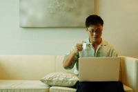 Man using laptop and holding cup - Alex Microstock02