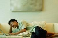 Man lying on sofa, using laptop - Alex Microstock02