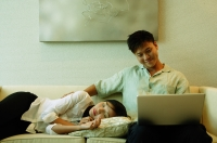 Man sitting on sofa, using laptop, woman lying next to him - Alex Microstock02