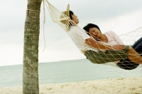 Couple lying in hammock on beach, sleeping - Jade Lee