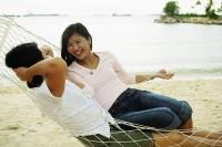 Couple in hammock on beach, talking - Jade Lee
