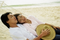 Couple lying in hammock on beach, eyes closed - Jade Lee