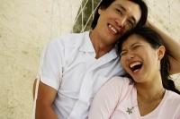 Couple lying in hammock on beach, laughing - Jade Lee