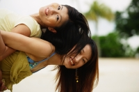 Young woman carrying friend on back, looking at camera - Jade Lee