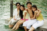 Couples sitting side by side on jetty, arms around each other - Jade Lee