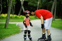 Father and daughter wearing inline skates, standing face to face - Jade Lee