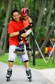 Father carrying daughter, both wearing inline skates - Jade Lee