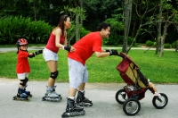 Family wearing roller blades, skating all in a row, father pushing stroller - Jade Lee