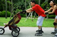 Father skating and pushing stroller, mother holding on to waist - Jade Lee