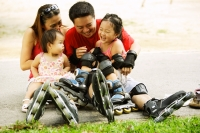 Family with two children sitting on ground, bonding - Jade Lee
