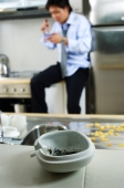 Man in kitchen, ashtray and cigarette in foreground ( selective focus) - Jade Lee
