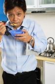 Man in kitchen, eating bowl of cereal, looking at camera - Jade Lee